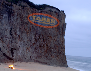 Taber construction logo projected on a cliff-face at dusk.