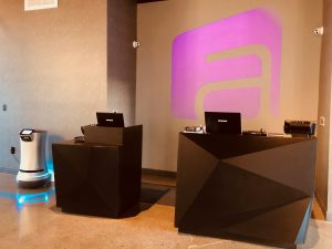 The Zenique Hotel projects their logo in purple behind the front desk.