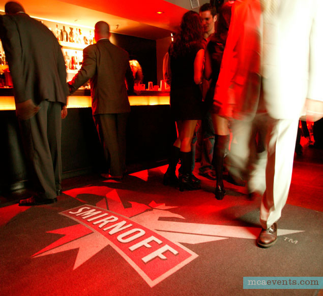 As people walk through a busy hotel bar, a motion sensor triggers the Smirnoff logo to project onto the floor.