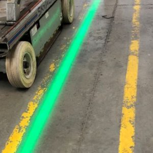 Green virtual walkway line projected next to faded yellow painted walkway.